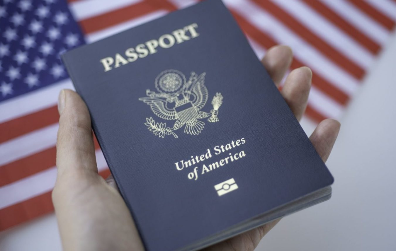 fingers holding Passport of USA on blurred American flags background. Close up view